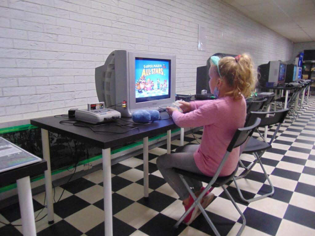 Dziewczynka grająca na NES jednym z eksponatów muzeum